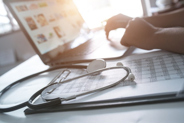 physician documenting billing on computer